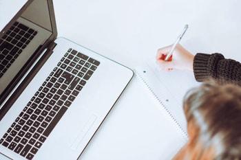 Femme qui écrit sur un carnet - créer et déposer sa marque